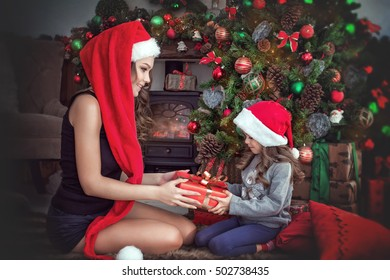 The beautiful young mother makes to the little daughter a Christmas gift.