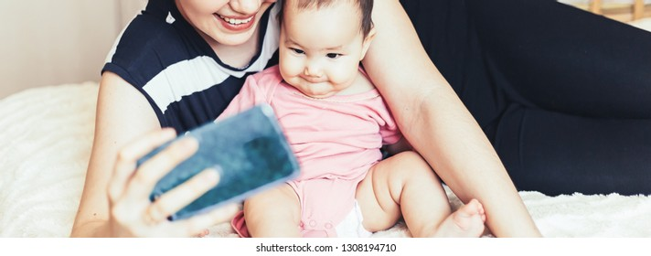 Beautiful young mother is making selfie with her adorable little baby and smiling while sitting on sofa at home long banner