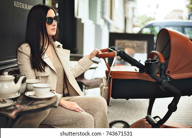 A beautiful young mother with a newborn baby in a stroller drinks tea in a street cafe. Fashionable modern mom with a baby in a cafe.