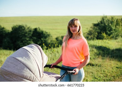 Beautiful young mother on a walk with a stroller.