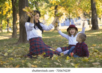 Beautiful young mother plays with her children in the park in autumn. They are having a good time while playing with the dry fallen leaves.