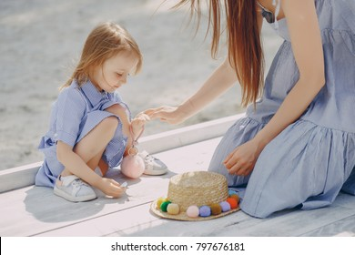 A beautiful young mother plays on the beach with her little daughter