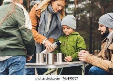 beautiful young mother pouring tea from thermos for kids on camping trip