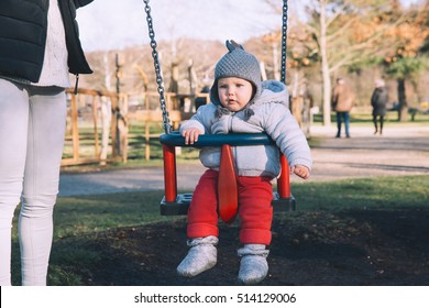 Beautiful young mother shakes her baby on swing at the playground on sunny day outdoors. Happy family dressed in warm clothes spend time together.