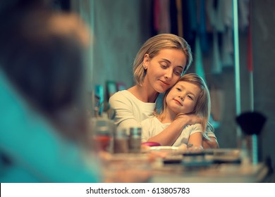 Beautiful young mother is sitting in front of the mirror of dressing table with her little daughter on her knees hugging her. Image with selective focus and toning