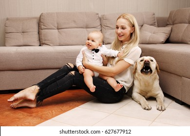 Beautiful young mother with a small child and with a dog. Happy mother with a child playing with a labrador in a house near the couch