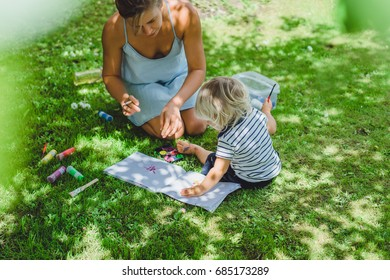 Beautiful young mother with a small child draws in the garden on the lawn. Mom and her son paint on the nature.