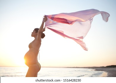 Beautiful young mother smiling against sunset sky, holding silk fabric up floating in breeze, body silhouette on summer holiday beach, outdoors. Healthy pregnancy beauty, leisure wellness lifestyle.