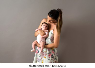 A beautiful young mother standing and holding her baby girl in her arms in front of a grey background in a studio.