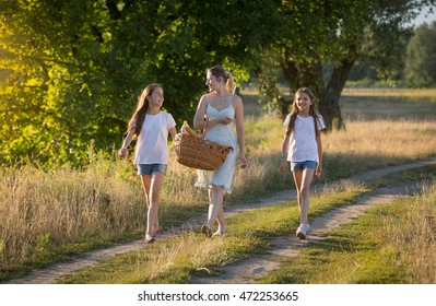 Beautiful young mother walking with her daughter in meadow at sunset