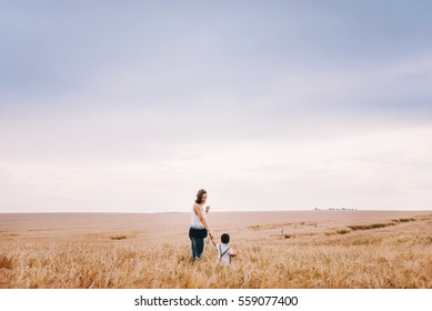 beautiful young mother walking with her young son on the wheat field. mom holds him gently by the hand, hugs and throws up in the sky
