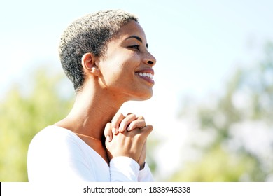 Beautiful young multicultural woman in the park on a clear, sunny day turned to the side for a closeup profile portrait while she clasps her hands in gratitude outside