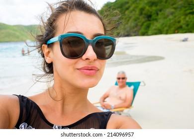 Belle jeune femme multiculturelle prenant un selfie sur une plage des Caraïbes.