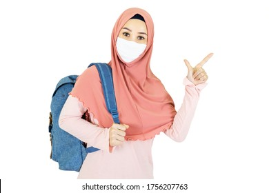 beautiful young muslim asian woman with traditional dress wearing medical face mask  to go to school Under the outbreak of the virus isolated on white background,health care concept