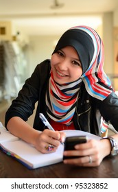 Beautiful young muslim  college girl with book and smile