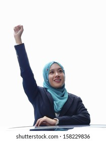 Beautiful young Muslim girl raises her hands isolated background