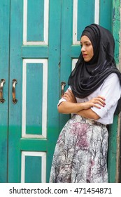 Beautiful young muslim lady  in Islamic dress look so sad while cross one arm standing in  front of close green wood door.