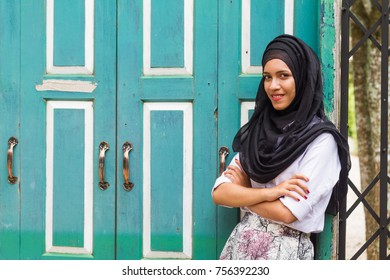 Beautiful young muslim lady  in Islamic dress smile while cross one arm standing infront of close green wood door.