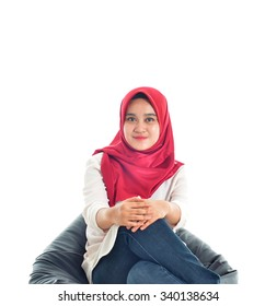 Beautiful young muslim pose while relaxing on a sofa. Isolated on white background.