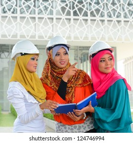 Beautiful young muslim woman in helmets on a construction site