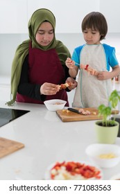 Beautiful young Muslim young woman with little boy at home working in kitchen