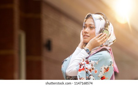 Beautiful young muslim woman wearing hijab and listening to music with wireless earphones