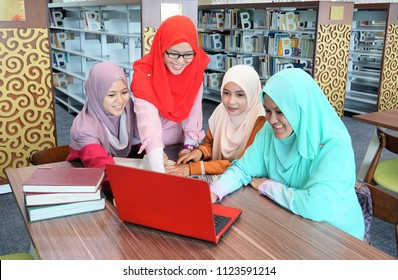 Beautiful young Muslimah students from Southeast Asian with hijab looking to the laptop and having discussion in the library.