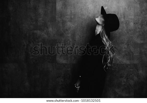 Schönes junges mysteriöses blondes Mädchen auf schwarzem Hut und schwarzer Jacke auf grauem Hintergrund. Die Augen sind mit einem Hut bedeckt. Maniküre - lange rote Nägel, Nagellack. Mode, Schönheit.