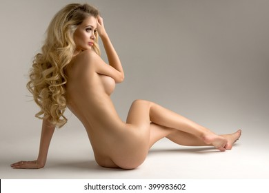 Beautiful young naked blonde woman sitting over the background