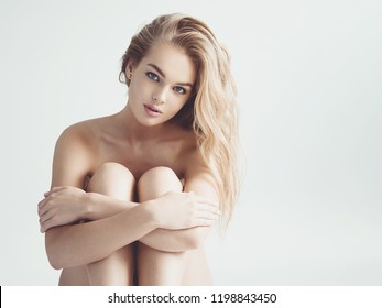 Beautiful young naked woman sits over the grey background. Gorgeous  woman with nude body. Nice portrait of a blonda girl with long curly hair.