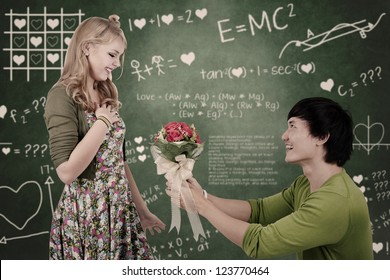 Beautiful young nerd girl gets flowers from her boyfriend in a classroom
