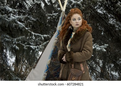 Beautiful young nordic rad haired girl in north ethnic clothes standing in the winter forest landscape near the wigwam