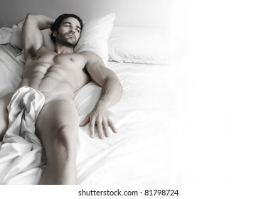 Beautiful young nude muscular male model alone in bed with lots of white copy space