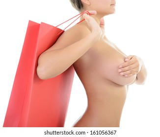Beautiful young nude woman holding red shopping bag covering her brest, over white background