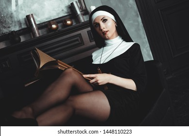 Beautiful young nun in religion black suit holds Bible and posing on camera with big book on a black background. Close-up. Religion concept.