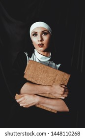 Beautiful young nun in religion black suit holds Bible and posing on camera with big book on a black background. Religion concept.