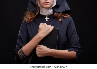 Beautiful young nun in religion black suit holds Bible and posing on camera with big book on a black background. Copy space. Close-up of cute nun. Religion concept.