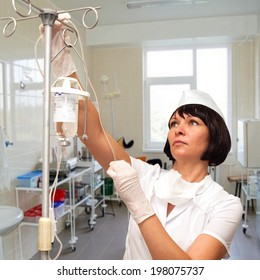 Beautiful young nurse preparing to hold intravenous drip medication