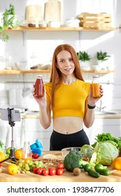 Beautiful young nutritionist woman having online video call via smartphone to showing detox handmade smoothie