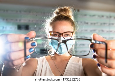 Beautiful young Optical Assistant wearing a face mask showing a pair of glasses