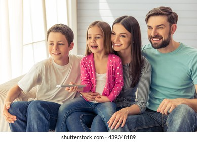 Beautiful young parents, their cute little daughter and son are watching TV and smiling, sitting on sofa at home. Girl is using a remote control
