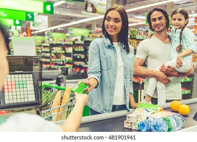 Beautiful young parents and their cute little daughter are smiling while standing near cash desk in the supermarket. Mom is giving a credit card