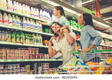 Beautiful young parents and their cute little daughter are smiling while choosing food in the supermarket. Girl is sitting on her dad's shoulders