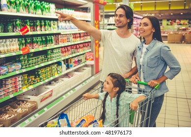 Beautiful young parents and their cute little daughter are smiling while choosing food in the supermarket. Girl is sitting in the shopping cart