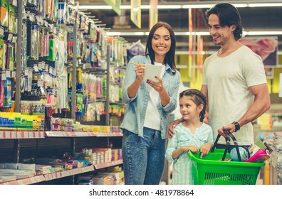 Beautiful young parents and their cute little daughter are smiling while choosing school stationery in the supermarket. Mom is making notes in the list
