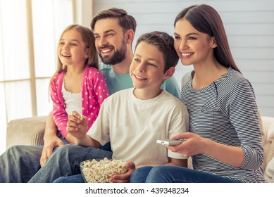 Beautiful young parents, their  daughter and son are watching TV, eating popcorn and smiling, sitting on sofa at home. Mom is using a remote control