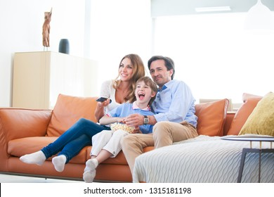 Beautiful young parents and their son are watching TV, eating popcorn and smiling while sitting on couch at home