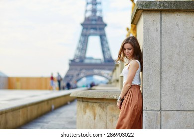 Beautiful young Parisian woman in long skirt near the Eiffel tower on a summer day