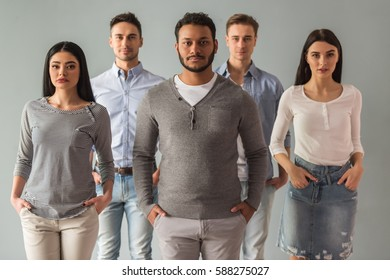 Beautiful young people in casual clothes are looking at camera, on gray background
