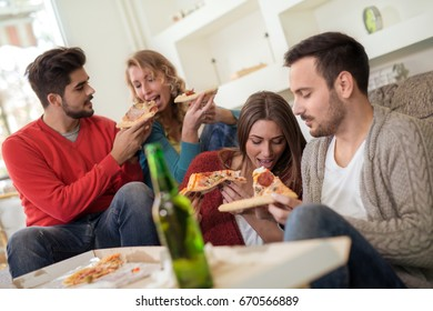 Beautiful young people in casual clothes are resting with pizza and bottles of drink, talking and smiling